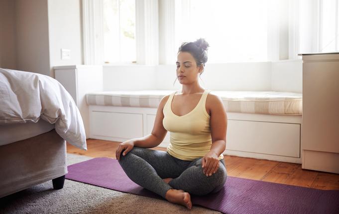 une femme médite en position du lotus dans sa chambre