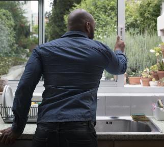 un homme ouvre la fenêtre de la cuisine